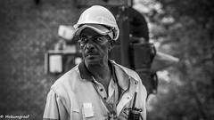 Man at work (Pieter van de Ruit) Tags: man work street netherlands blackwhite olympusem1 bw streetphotography moustache earring building helmet
