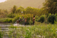 Children playing football in the river,Asia's rural lifestyle and nature. (Visoot20) Tags: soccer children playing ball football goal river field player stadium light play sport activity competition athlete foot champion shoot winner people background white life success power boy team game strong win running competitive exercising nature sunset action lifestyle africa green west storm sierra leone red person woman summer symbol