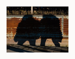 Morning walk (ulf_finndahl) Tags: city shadow shadowplay urban minimalism urbanminimalism rust fence people ulffinndahl gothenburg sweden streetphoto streetphotography street brown restaurant light sun silouette walk pavement outdoor morning