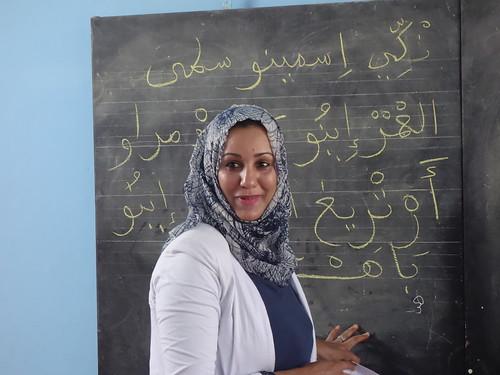 Majida, l'enseignante de français, entrain d'écrire en arabe au tableau