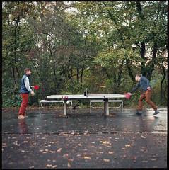 Ping Pong (Konrad Winkler) Tags: berlin hasenheide park tischtennis pingpong männer bier laub herbst kodakektar100 langzeitbelichtung mittelformat 6x6 hasselblad503cx epsonv800