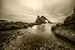 "fine art black & white moody long exposure shot of Bow Fiddle Rock, Moray, Scotland (grumpybaldprof) Tags: bw blackwhite ""blackwhite"" ""blackandwhite"" noireetblanc monochrome ""fineart"" striking artistic interpretation impressionist stylistic style contrast shadow bright dark black white illuminated moray scotland uk ""bowfiddlerock"" portknockie ""naturalseaarch"" arch sea ""northsea"" sandstone quartz tourist seagulls nesting birds port harbour waves rock bow fiddle water sky cloud texture cliff erosion canon 7d ""canon7d"" sigma 1020 1020mm f456 ""sigma1020mmf456dchsm"" wideangle ultrawide"