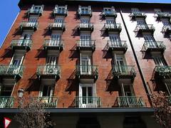 Madrid Apartments (RubyGoes) Tags: balconies bricks white doors louvre black red tree blue sky spain lamp
