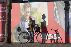 Waiting girl (Jan van der Wolf) Tags: map17241v girl vrouw woman bike streetphotography straatfotografie shadow shadows shadowplay schaduwspel street straat poster wall people candid fiets leiden waiting wachten cover pomotion billboard reclame publicity