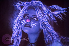 Cheshire Cat (Paulann_Egelhoff) Tags: paulann paulannegelhoff photography professional art artist design designer phoenix mesa az arizona special event blacklight party uv light purple blue glow glowing unique weird costumes cosplay fantasy alice wonderland aliceinwonderland theme themedparty models guests dark bright colorful people indoors night noflash halloween tea teaparty cheshire cheshirecat cat fur furry sexy sexycosplay