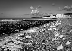 Stepping Stones...an alternative perspective. (Lloyd Austin) Tags: composition nikon d5100 sevensisters bnw blackandwhite bw mono monochrome dramatic nature beautiful england birlinggap eastsussex open vast cloudscape clouds sky view people landscape chalk cliffs waves tide water ocean seascape sea coastline coastal sand beach shoreline shore rocks pebbles stones perspective alternative steppingstones