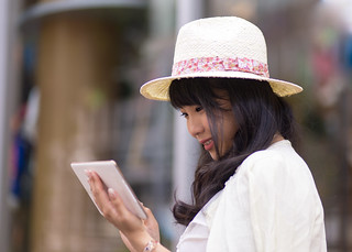 Young woman looking at digital tablet on street