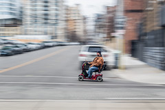Cruising the streets of Toronto (HisPhotographs.com) Tags: panning toronto 18thshutter slowshutter scooter red bluejeans cap hat man cruising motion action queenstreet downtown city blur street intersection motorized mobility aid mobilityaid jacket inbetweenthelines