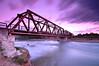 Bridge over time (Gabriel Panaiet) Tags: nikon nikond300 tokina1224 tokina bridg clouds morning pink trail rails metal grass water reflections