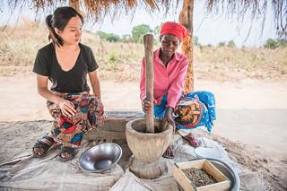 A research intern watching the production of fish powder, Zambia. Photo by Chosa Mweemba.