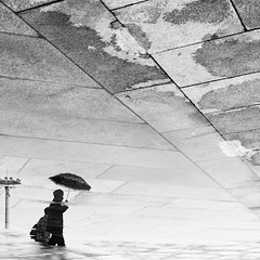 Black mirror (Go-tea 郭天) Tags: pékin beijingshi chine cn beijing tiananmen square water puddle reflection mirror wet rain umbrella pavement candid view man walk walking street urban city outside outdoor people bw bnw black white blackwhite blackandwhite monochrome naturallight natural light asia asian china chinese canon eos 100d 24mm prime corner floor ground