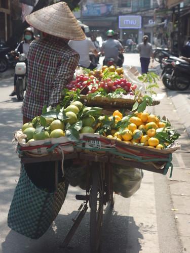 une dame transportant des fruits sur son vélo