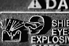 !Danger: Macro Mondays - Sidelit (thatSandygirl) Tags: blackandwhite monochrome face goggles safety graphics graphicdesign warning explosion lines macromondays sidelit bokeh depthoffield texture battery car auto automotive
