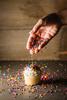 Sprinkling the Sprinkles (runrgrl661) Tags: cupcake sprinkles hand food movement macro offcameraflash