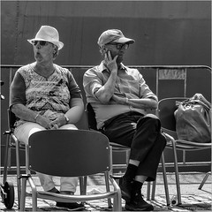 Watching the world go by (John Riper - OFF FOR AWHILE) Tags: johnriper street photography straatfotografie square vierkant bw black white zwartwit mono monochrome netherlands candid john riper rotterdam marine port worldportdays wereldhavendagen fuji fujifilm xt2 18135 silent hedonists watching people hats chairs enjoying cap hat bag