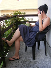 Outdoor Office:) (sean and nina) Tags: nina seated sitting chair balcony plant green leaves fence wood wooden shade petrinja croatia croatian hrvatska serb female lady girl woman girlfriend fiancee wife married blue summer dress legs feet sandals shoulders neck throat face profile brunette dark brown hair telephone conversayion candid outdoor outside coffee drinking cup tan tanned skin bare beauty beautiful gorgeous stunning charm charming cute eu europe european balkan balkans flip flops