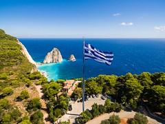 Greek biggest national flag waving in the sky in Keri in Zakynthos (Zante) island in Greece (altextravel) Tags: aerial architecture beautiful blue cave cliff country culture day destination europe flag greece greek holiday ionian island keri landscape lighthouse mediterranean national ocean outdoors santorini sea sky summer symbol tourism traditional travel turquoise waving white wind zakinthos zakynthos zante