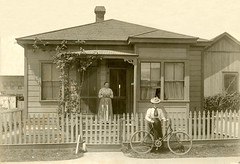 A Woman and Her Bicycle (Alan Mays) Tags: ephemera photographs photos foundphotos portraits cardboard borders women bicycles bicyclists bikes hats dresses clothes clothing houses homes houseproud yards fences picketfences porches antique old vintage