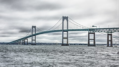 Pell Bridge with Newport Behind (Ian Charleton) Tags: pellbridge claibornepellbridge newport rhodeisland newportbridge jamestownisland narragansettbay coast shore water seascape landscape architecture sky clouds ocean sea desaturated