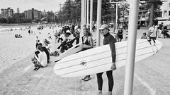 Ride on! (geemuses) Tags: surf surfers surfing man woman sea water sand beach landscape bw black white bandw ocean street streetphotography portrait lumix panasonic candid people blackandwhite surfboard