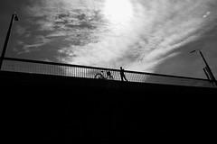 Short stop on the bridge (Mikhail Korolkov) Tags: street bridge silhouette bicycle streetlights sun clouds bw blackandwhite monochrome fujifilm xe2 xf1855mm