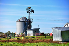Barnyard Sentry_175810 (rjmonner) Tags: windmillwednesday iowa barnyard farm farming rural windmill gate fence grainbin shed agriculture agronomy tires feedbunk