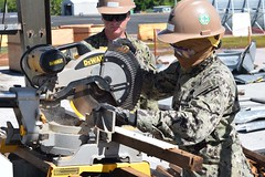 Seabee cuts material from a demolished building to remove from a project site.