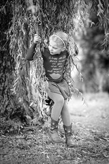 Girl playing with a willow tree swing (Mark van Oirschot) Tags: girl blackandwhite bw boxtel kid happy playfull family fuji fuji56mm fujixt2 nice smooth nature willow willowtree foliage tree grass pigtails