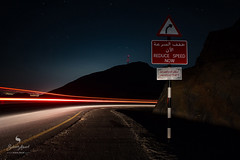 REDUCE SPEED NOW (hisalman) Tags: light trail longexposure road sign mountain outdoor night dark hisalman canon