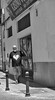 Superman On Vacation (tcees) Tags: callefuerteventura grantarajal canaryislands fuerteventura canaries superman people bw blackandwhite street streetphotography x100 fujifilm posts bollards pavement sidewalk wall window bar shop shadow cables urban