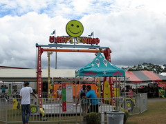 Wade Shows Happy Swing Ride. (dccradio) Tags: lumberton nc northcarolina robesoncounty cloudy overcast carnival midway fairride amusements amusementdevice mechanicalride ride rides thrillride outdooramusement fun entertainment outdoors outside grass lawn yard lot ground greenery robesonregionalagriculturalfair fair countyfair robesoncountyfair communityevent canon powershot a3400is wade wadeshows mum mums happyswing zamperla star foodstand fairfood tent face flag flags bluesky clouds fence ridefence trashcontainer garbagebin canopy