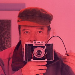 reflected self-portrait with Agifold III camera and corduroy cap (crop) (pho-Tony) Tags: square cameraselfportraits xpro fujivelvia agifoldiii agilux agifold iii agiluxagifoldiii madeinengland england english 6x6 6cmx6cm 66 120 rollfilm roll film visualextinctionmeter visual extinction meter rangefinder 75mm 75mmanastigmat anastigmat f45 145 bellows folding folder mediumformat iso100 expired fuji velvia 100 slide crossprocessed tetenal