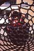 Swinging it (Magnus Bergström) Tags: canon ae1 expired 135 film 35mm analog fuji provia 100f fujiprovia100f fujichromeprovia100frdpiii fujichrome sverige sweden karlstad värmland swing child boy hat mesh web portrait houe building people window play playground lovnil00