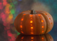 party pumpkin for macro mondays 'hallowe'en' (Emma Varley) Tags: pumpkin halloween carved party bokeh bright colourful lights candle reflection glass macromondays