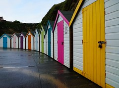 Beach Huts (JamieHaugh) Tags: newquay cornwall england uk sony a6000 color colour outdoors beach huts yellow pink blue green orange purple house shelter shacks sheds rain wet reflection water britain