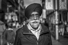 An Act of Sincerity (Leanne Boulton) Tags: portrait urban street candid portraiture streetphotography candidstreetphotography candidportrait streetportrait eyecontact candideyecontact streetlife old elderly man male face facial expression eyes look emotion feeling mood sikh turban distinguished gentleman beard moustache expressive tone texture detail depthoffield bokeh naturallight outdoor light shade shadow sunlight city scene human life living humanity society culture people canon canon5d 5dmarkiii 70mm character ef2470mmf28liiusm black white blackwhite bw mono blackandwhite monochrome glasgow scotland uk