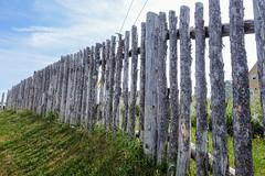 Beyond the Fence (gabi-h) Tags: ryanpremises bonavista newfoundlandandlabrador fence fencefriday wooden shadows gabih grass historical historicalsite bluesky clouds fenceline