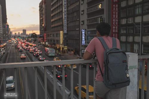 台北生活- 來來回回的天橋上,總有許多人駐足在這拍風雨前的日落,唯有這位兄台他靜靜的望著尖峰時段的車流,車燈像回憶的霓虹般飄向遠方。