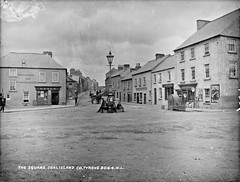 Square, Coalisland, Co. Tyrone (National Library of Ireland on The Commons) Tags: robertfrench williamlawrence lawrencecollection lawrencephotographicstudio thelawrencephotographcollection glassnegative nationallibraryofireland thesquare coalisland cotyrone lytlesshop ulster tyrone northernireland countytyrone mainstreet dogs stpatrickshall premierbicycles francisvincentfullen lytle fullen bsafittings tullyniskane ulysses