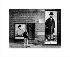 Lautrec vs Jagger (tkimages2011) Tags: jagger toulouse lautrec poster street person wall mono monochrome blackandwhite albi france bricks barefoot