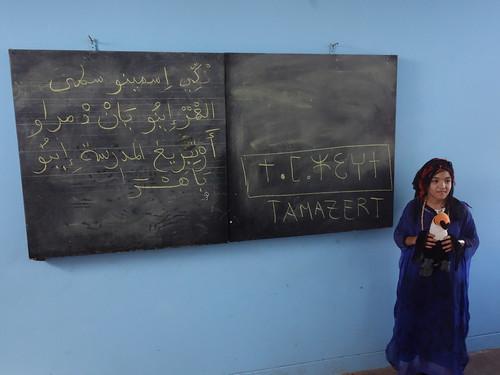 Selma en tenue traditionnelle berbère et devant des écritures arabes et amazight