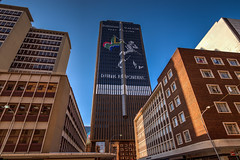 Johnny Walker (Paul Saad) Tags: johannesburg nikon street building architecture road city skyscraper sky sign intersection gauteng long flickr cbd capital joburg photowalkers tree people