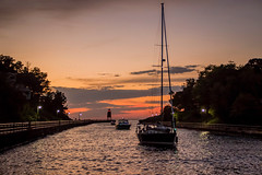 Sailing Home (T P Mann Photography) Tags: sun sunlit river water sail sailboat boat yacht channel lake michigan light lighthouse pier walkway railing lamppost clouds sky dusk sundown evening low red green lights pure shadows silhouette reflections charlevoix ngc