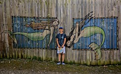 Boy in the Company of Mermaids (ricko) Tags: issac grandson fence mermaids paintings kcrenaissancefestival bonnersprings kansas