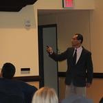 Dr. Kang-Na flips through a slideshow during his presentation.