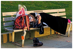 Halloween on a Park Bench (HereInVancouver) Tags: youngwoman costume death relaxing layingdown seawall vancouverswestend texting halloween whiteface pinksocks lifeonaparkbench candid streetphotography canong3x vancouver bc canada