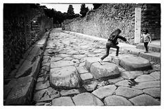 Main Street, Pompeii (halifaxlight) Tags: italy campania pompeii historicsite ruins remains street walls steppingstones children kids stepping jumping fun bw
