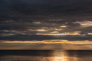 The golden sunrise behind dark skies of mourning