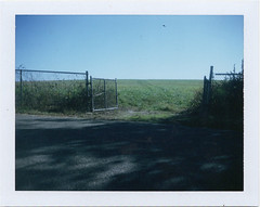 Gated (m.ashe7) Tags: polaroid polaroid440 fp100c fuji packfilm outdoors meadow field fences gated tiretracks path blueskies