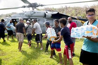 Sailors and local volunteers unload drinking water from an MH-60S Sea Hawk helicopter